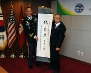 "SEOUL, Korea — Suh Jin-Sup (right), Chairman of the ROK-U.S. Alliance Friendship Association, presents Col. Donald E. Degidio, Jr., Commander of the U.S. Army Corps of Engineers, Far East District, a scroll with ""Jeon Taek-Hee,"" Degidio's new Korean name written in Hanja, traditional Korean characters, May 10 at the Korea Ministry of National Defense."