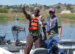 "CALIFORNIA — A veteran and a local volunteer showoff their catch during the ""Take a Warrior Fishing"" event at Eastman Lake, Calif., May 12, 2012. The event was the first of its kind for the U.S. Army Corps of Engineers Sacramento District."