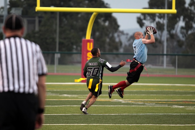 """Brandon Charles intercepts a pass during the 2012 Flag Football Championship League on Camp Pendleton, May 17. """"The Gators were the toughest team we have gone up against in this tournament,"""" said Jay M. Johnson, coach of the Combat Logistics Regiment 17 Desk Jockeys. """"I have to say the turning point came down to one great catch."""" Charles is the cornerback for Desk Jockeys."""