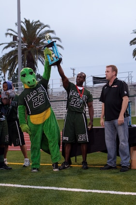 The Assault Amphibious School Battalion Gators mascot and Brian Richardson hold up the second place trophy given to them during the 2012 Flag Football Championship League on Camp Pendleton, May 17. Every player on both teams recieved medals for making it to the finals. Richardson is the offensive coach for the Gators.