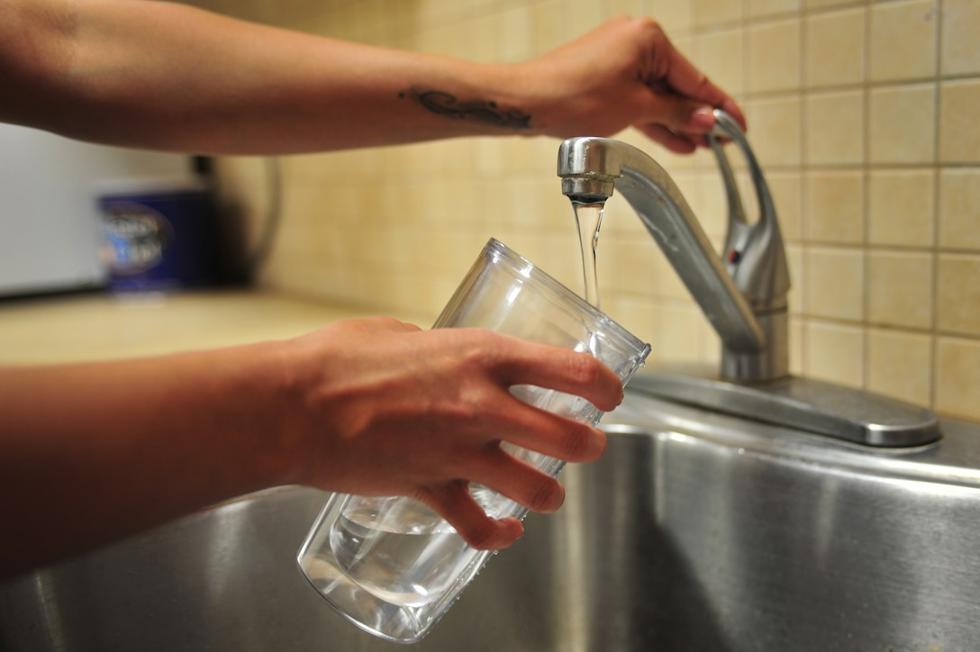 A U.S. Air Force service member pours herself a glass of tap water from a break room at Cannon Air Force Base, N.M., May 10, 2012. The local areas have a higher than naturally occurring fluoride level in their water systems which raises concerns of fluorosis, a condition that can cause permanent staining and pitting or mottling of the teeth. (U.S. Air Force photo by Airman 1st Class Alexxis Pons Abascal)