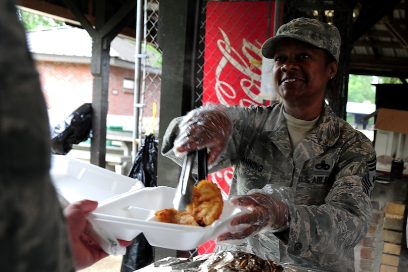 Chief Master Sgt. Gigi Manning, command chief of the 315th Airlift Wing, serves fish at the Chiefs Annual Fish Fry, May 18 on Joint Base Charleston - Air base, S.C.  The fish fry began as a barbeque in 1987 and was a way to unite the Reserve and active-duty members on the air base.  (U.S. Air Force photo/ Staff Sgt. Nicole Mickle)
