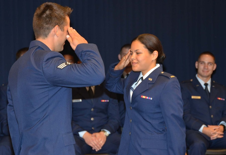 University of New Mexico Air Force ROTC graduate 2nd Lt. Michelle Moldovean receives her first salute as an officer from her husband Senior Airman Paul Moldovean, Detachment 1, 342nd Training Squadron at Kirtland AFB, N.M., during a May 11, 2012 graduation and commissioning ceremony held at the Air Force Operational Test and Evaluation Center at Kirtland.