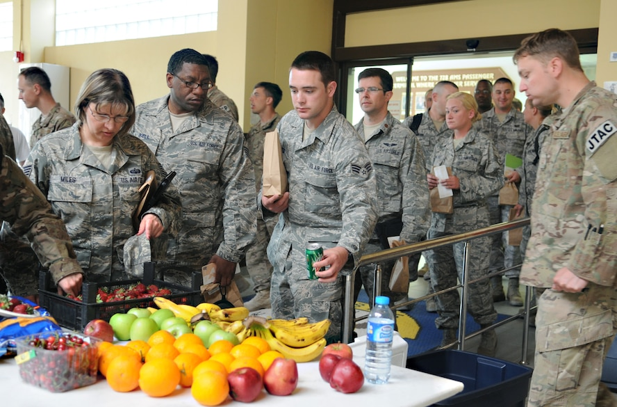 Service members returning from deployments on a layover at the Incirlik passenger terminal wait in line for fruit provided by Operation First Stop May 12, 2012 at Incirlik Air Base, Turkey. Operation First Stop is a community service project created by Incirlik Airman Leadership Class 12-D to provide snacks and drinks to redeploying service members traveling though Incirlik. (U.S. Air Force photo by Senior Airman Marissa Tucker/Released)
