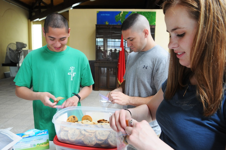 From left, Senior Airman Conrad Zamora, Staff Sgt. Benjamin Pecarina and Senior Airman Danielle Denny, graduates of Incirlik Airman Leadership School Class 12-D, pack cookies into small bags to distribute to more than 250 redeploying service members during Operation First Stop May 12, 2012, at the passenger terminal Incirlik Air Base, Turkey. Operation First Stop is a community service project created by Class 12-D to provide snacks and drinks to redeploying service members traveling though Incirlik. (U.S. Air Force photo by Senior Airman Marissa Tucker/Released)