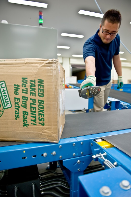 YOKOTA AIR BASE, Japan -- Yazuru Kimura, Detachment 2, Pacific Air Forces Postal Squadron mail sorting supervisor, scans a box at Yokota Air Base, Japan, May 10, 2012. Scanning pieces of mail allows the transit, time and location to be tracked. (U.S. Air Force photo by Airman 1st Class Krystal M. Garrett)