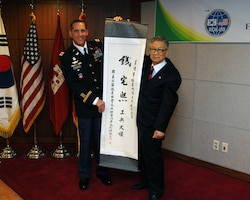 "Suh Jin-Sup (right), Chairman of the ROK-U.S. Alliance Friendship Association, presents Col. Donald E. Degidio, Jr., Commander of the U.S. Army Corps of Engineers, Far East District,  a scroll with ""Jeon Taek-Hee,"" Degidio's new Korean name written in Hanja, traditional Korean characters, May 10 at the Korea Ministry of National Defense."