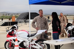 Col. Mike Lawrence, commanding officer of Marine Corps Air Station Camp Pendleton, speaks with a Marine about her unique, custom motorcycle during Semper Ride's Fun Day on the Runway at the Marine Corps Air Station Camp Pendleton, May 18.