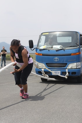 Anita Clayton, a 131 pound and above competitor, pulls a two and a half truck during the 2012 Strongman Competition at Penny Lake Field Here May 19, 2012. The competition consisted of several events including a Farmer's Walk, tire flip, barrel press and truck pull. A total of 10 competitors, three males and seven females, participated in two classes for females and three for males.