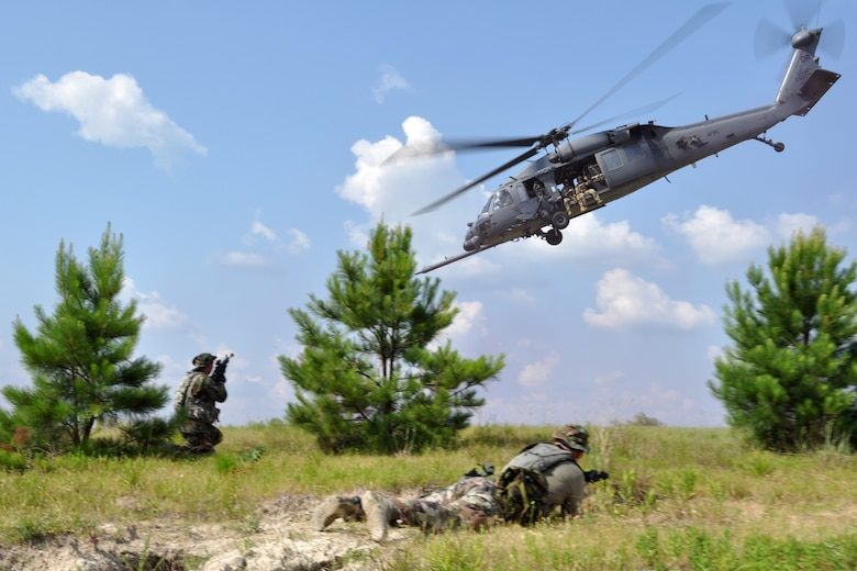 OPFOR (Opposing Force) unit members make a final attack on an HH-60 helicopter as it extracts a group of pararescuemen from the 929th Rescue Wing off the battlefield at Fort Polk, La., May 16, 2012. The Airmen were part of a combat search and rescue (CSAR) mission to rescue two downed pilots during the Patriot Saint exercise. (U.S. Air Force photo by Master Sgt. Jeff Walston/Released)
