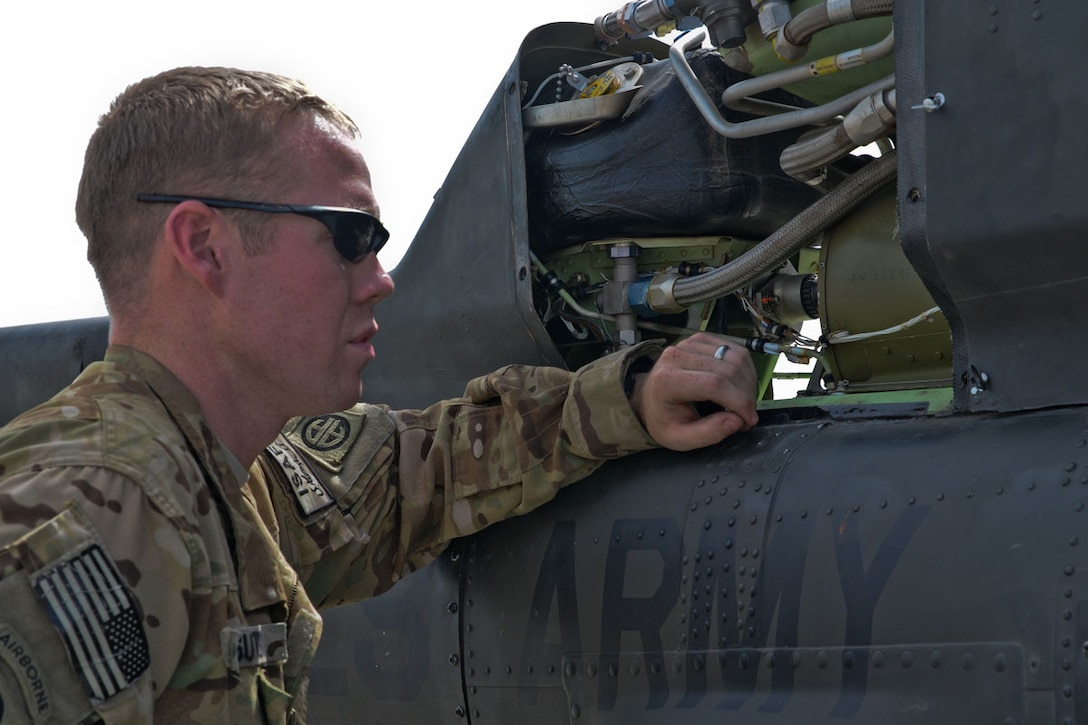 U.S. Army Sgt. Brandon Sutton, a crew chief with A Troop, 1-17 Cavalry, hailing from Dallas, works on a Kiowa Warrior OH-58D (R) helicopter at Forward Operating Base Salerno May 9. (U.S. Army Photo/Spc. Eric-James Estrada)