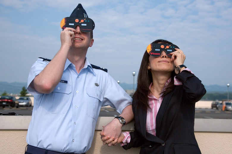 "YOKOTA AIR BASE, Japan -- Capt. Drew Jernigan, 374th Airlift Wing legal office, and his wife Makiko enjoy watching the annular solar eclipse at Yokota Air Base, Japan, May 21, 2012. The annular solar eclipse, takes place when the moon covers as much as 94 percent of the sun resulting in a ""ring of fire"". (U.S. Air Force photo by Osakabe Yasuo)"