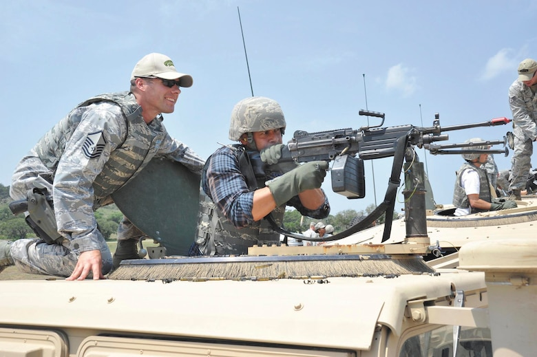 Master Sgt. Brandon Hannasch, flight chief, Basic Officer Course, guides actor Jon Huertas as he lays down a burst of suppressive fire from an M249 machine gun during a simulated assault May 4 at Camp Bullis. (U.S. Air Force photo/Alan Boedeker)