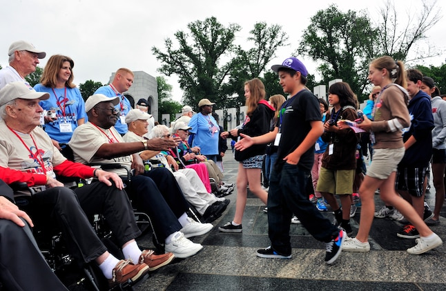 Middle School Students greet World War II veterans by shaking their hands and presenting them a small American flag outside the WWII memorial in Washington D.C. The trip is part of a program called the Greater St. Louis Honor Flight, a non-profit that takes World War II veteran to the to the memorials.  The WWII memorial honors the 16 million who served in the armed forces of the U.S. during World War II, the more than 400,000 who died, and the millions who supported the war effort from home. Symbolic of the defining event of the 20th Century, the memorial is a monument to the spirit, sacrifice, and commitment of the American people to the common defense of the nation and to the broader causes of peace and freedom from tyranny throughout the world. The memorial opened to the public on April 29, 2004 (U.S. Air Force photograph/ Staff Sgt. Stephenie Wade)