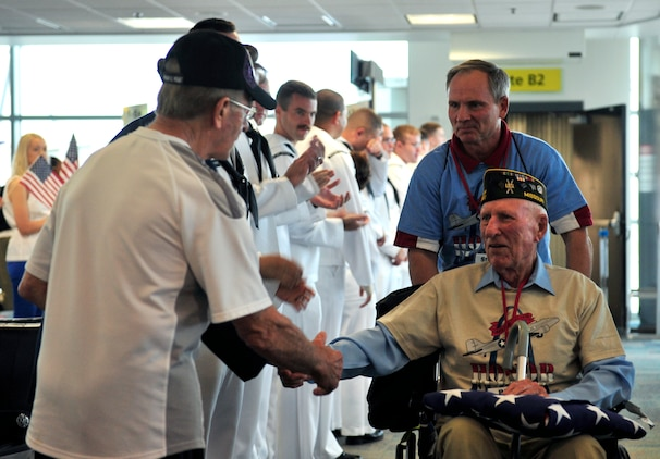 Dave Hinrichs, an 83-year-old Army veteran is greeted by members of the Navy May 21, as he departed an aircraft for a tour of Washington D.C. memorials. Military members greeted the veterans upon their arrival in D.C and in St. Louis when arriving home.  (U.S. Air Force photograph/ Staff Sgt. Stephenie Wade