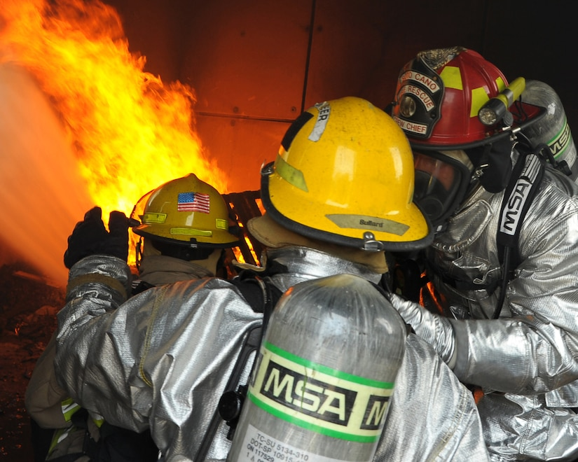 SOTO CANO AIR BASE, Honduras - Honduran firefighters put out a mock-structural fire as a U.S. Air Force firefighter instructs the pair on the procedures during Central America Sharing Mutual Operational Knowledge and Experiences (CENTAM SMOKE) exercise at Soto Cano Air Base, Honduras, May 9, 2011. CENTAM SMOKE takes place every quarter allowing firefighters from across Central America to come and share their firefighter knowledge during the four days of team-building training. (U.S. Air Force photo/Staff Sgt. Bryan Franks)