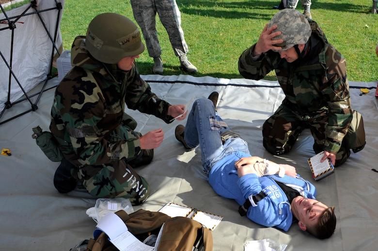 BUCKLEY AIR FORCE BASE, Colo. –  Lt Col. Shane Sullivan, right, 460th Space Wing chief of safety, and Airman 1st Class Jayce Yeager, 460th Civil Engineer Squadron, perform self-aid buddy care during the during an exercise, May 17, 2012.  Inspectors tested nearly 50 members of the 460th SW of skills they might need in an operational environment. (U.S. Air Force photo by Airman 1st Class Riley Johnson)