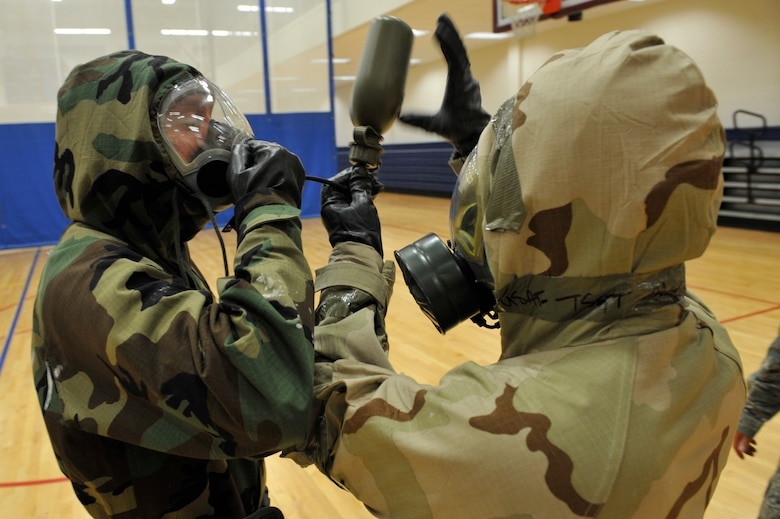 BUCKLEY AIR FORCE BASE, Colo. -- Staff Sgt. Jesus Almero, right, 460th Medical Group, helps Senior Airman Ashley  Appleby, 460th Comptroller Squadron, drink from his canteen,  May 16, 2012.  The ability to survive in a chemical environment was one of the many things the 460th Space Wing was inspected on during their Operational Readiness Inspection. (U.S. Air Force photo by Airman 1st Class Riley Johnson)