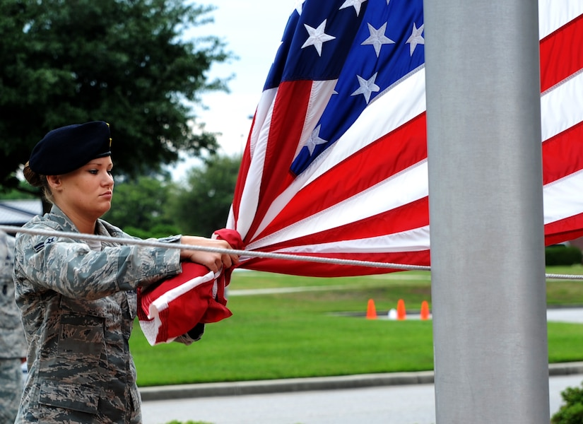 """Airman 1st Class Heather Ives, 628th Security Forces Squadron, lowers the flag during the """"National Police Week"""" retreat ceremony May 18, 2012 at Joint Base Charleston, S.C. During National Police Week, Security Forces members honor law enforcement personnel who have fallen.  Joint Base Charleston held other activities and events for Police Week to include a 'Guns and Hoses' competition against the 628th Civil Engineer Squadron and a Chili Cook Off. (U.S. Air Force photo/Airman 1st Class Ashlee Galloway)"""