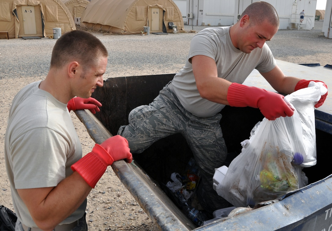 U.S. Air Force Staff Sgt. Jeff Kisamore (left) and Airman 1st Class Adam Cassada, 386th Expeditionary Civil Engineer Squadron Force Protection Flight Garbage Disposal Escort Team, rip open bags in a garbage dumpster during sweeps at an undisclosed location, Southwest Asia, May 16, 2012. The GDE Airmen go into the dumpsters twice, sometimes three times a day looking for things that can pose safety and security risks for U.S. and host nation personnel.  Kisamore is a Pelham, Ala., native deployed from the 18th Dental Squadron, Kadena Air Base, Japan.  Cassada is a Charlotte, N.C., native deployed from the 354th Operation Support Squadron, Eielson Air Force Base, Alaska. (U.S. Air Force photo/Tech. Sgt. Stacy Fowler)