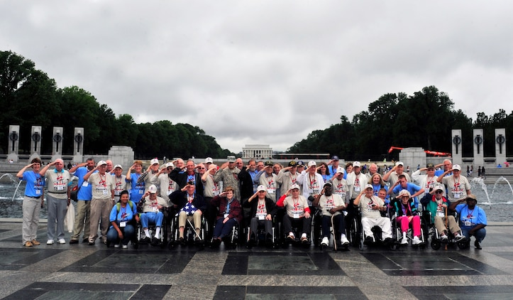 """On a trip to the Washington D.C. memorials 26 World War II veterans and their guardians pose for a group photo outside the WWII memorial May 21 during an Honor flight trip. Honor flight is a program that transports World War II veterans once a month to in Washington, D.C. to view the National World War II, Korean war, Lincoln and Vietnam memorial, the a viewing of """"The Changing of the Guard"""" at Arlington National Cemetery, Iwo Jima and ending with the U.S. Air Force memorial. For most of the veterans this was their first time viewing the memorials.  (U.S. Air Force photograph/ Staff Sgt. Stephenie Wade)"""