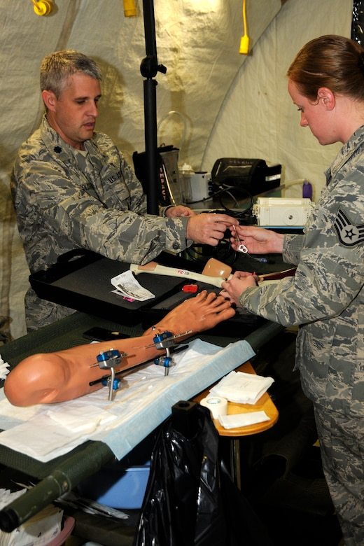 Lt. Col. Dr. Robert Goldtrap, 188th Medical Group, Arkansas Air National Guard, demonstrates a procedure to Staff Sgt. Jamie McClelland, 127th Medical Group, Michigan Air National Guard, during a training exercise at the Alpena Combat Readiness Training Center, Mich., May 23, 2012. The exercise brought together Airmen from eight medical groups from seven states. (U.S. Air Force photo by TSgt. David Kujawa)