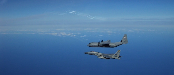 KEFLAVIK, Iceland -- During a NATO air policing exercise, a C-130J Super Hercules, deployed from Ramstein Air Base, Germany, is intercepted by an F-15C Eagle, deployed from Royal Air Force Lakenheath, England. The aircraft are major weapon systems of the 493rd Expeditionary Fighter Squadron, which is made up of both U.S. Air Force and NATO personnel fulfilling an air policing mission that assists in assuring Iceland's air sovereignty from May 12 to June 7, 2012. (Courtesy photo)