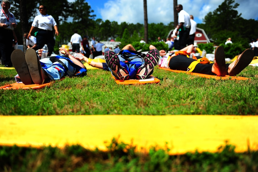 Role players acting as burn victims lay on stretchers while waiting for care during a mass causality exercise May 15, 2012 at the Amenity Center in The Farm at Wescott Plantation. Department of Health and Environmental Control District 7, in conjunction with Joint Base Charleston members, local emergency medical services, fire departments, law enforcement, coroners and all Charleston area hospitals conducted the live, mass causality incident readiness exercise to test first responder abilities and processes.    (U.S. Air Force Photo/Airman 1st Class Jodi Martinez)