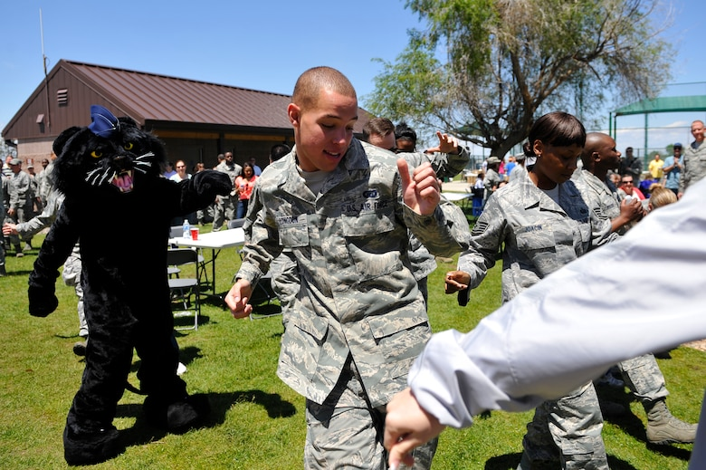BUCKLEY AIR FORCE BASE, Colo. -- Buck Lee, 460th Space Wing mascot, left, and Airman 1st Class Michael Longdon, 460th Contracting Squadron, center, dance with other members of the 460th SW May 24, 2012. Music, games and barbecue was offered at Buckley's Post-Operational Readiness Inspection Party. (U.S. Air Force photo by Staff Sgt. Kathrine McDowell)