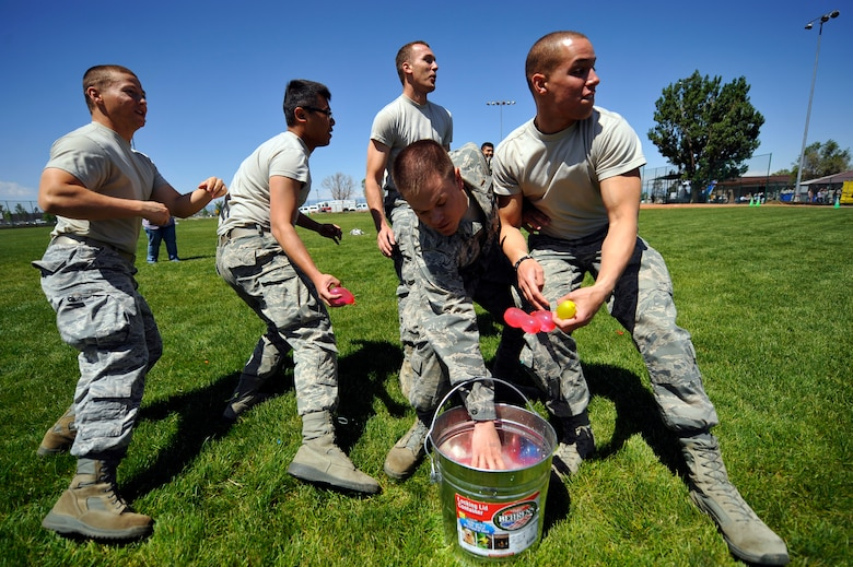 """BUCKLEY AIR FORCE BASE, Colo. -- 460th Space Wing members make their first move during a water balloon fight May 24, 2012. The 460th SW gathered together to celebrate earning an """"Excellent"""" rating during a recent Operational Readiness Inspection.  (U.S. Air Force photo by Staff Sgt. Kathrine McDowell)"""