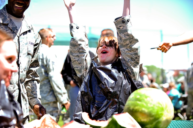 BUCKLEY AIR FORCE BASE, Colo. -- Airman 1st Class Danielle Keister,460th Security Forces Squadron pass and ID technician, celebrates as the winner of a watermelon eating contest May 24, 2012. Members of Team Buckley participated in a day of activities celebrating their excellent rating during their recent Operational Readiness Inspection. (U.S. Air Force Photo/ Senior Airman Paul Labbe)