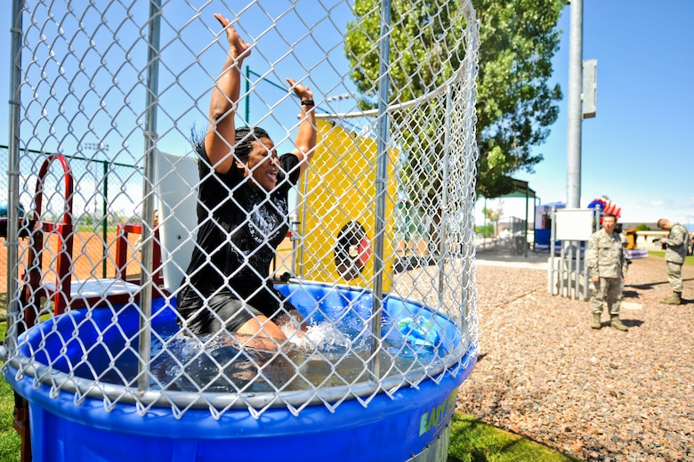 BUCKLEY AIR FORCE BASE, Colo. -- Maj. Halima Muhammad-Whitehead, 460th Force Support Squadron deputy, falls into a dunk tank May 24, 2012. Team Buckley  participated in a day of activities celebrating their excellent rating during a recent Operational Readiness Inspection. (U.S. Air Force Photo/ Senior Airman Paul Labbe)