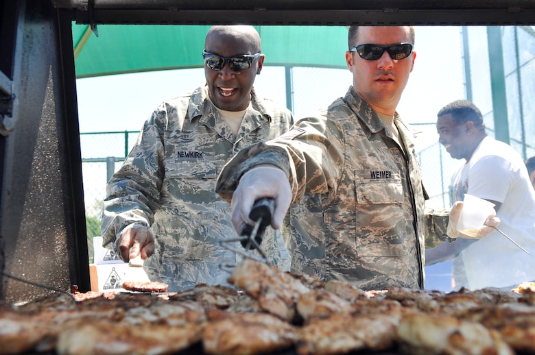 BUCKLEY AIR FORCE BASE, Colo. – Master Sgt. Darnell, left, of the 460th Medical Group, and Master Sgt. Shaun Weimer, of the 460th Space Communications Squadron, flip hamburgers and chicken as they volunteer to cook for those attending Team Buckley's Post-Operational Readiness Inspection Party May 24, 2012.