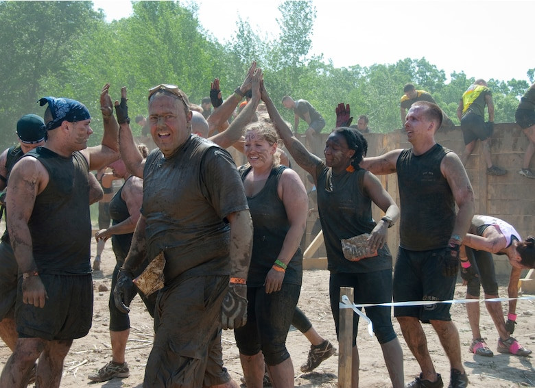 Members of the 109th Aeromedical Evacuation Squadron, Minnesota Air National Guard team celebrate getting over a tough obstacle at the Tough Mudder in Somerset, Wis. on May 19, 2012.  About a dozen Aeromeds made up one team and there were at least a dozen others from the 133rd Airlift Wing getting muddy for exercise, camaraderie, and to help raise money for the Wounded Warrior project.  U.S. Air Force Photo by Staff Sgt. Jonathan Young