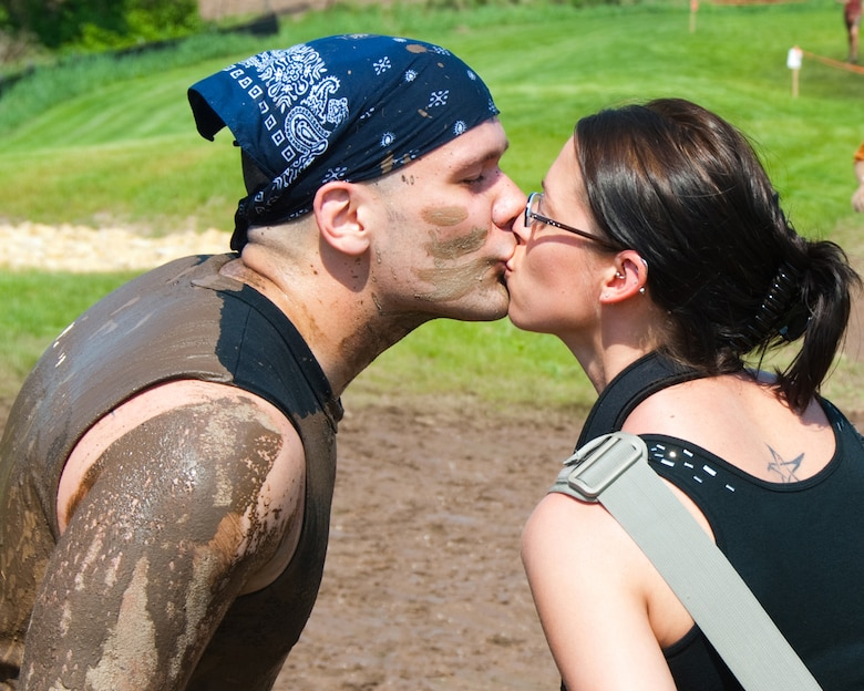 Minnesota Air National Guard member Staff Sgt. Greg White kisses his wife Tiffany during a quick break in the middle of the Tough Mudder obstacle course in Somerset, Wis. on May 19, 2012.  White had just returned from a deployment four days earlier, but still participated with a team of Airmen from the 109th Aeromedical Evacuation Squadron.  U.S. Air Force Photo by Staff Sgt. Jonathan Young