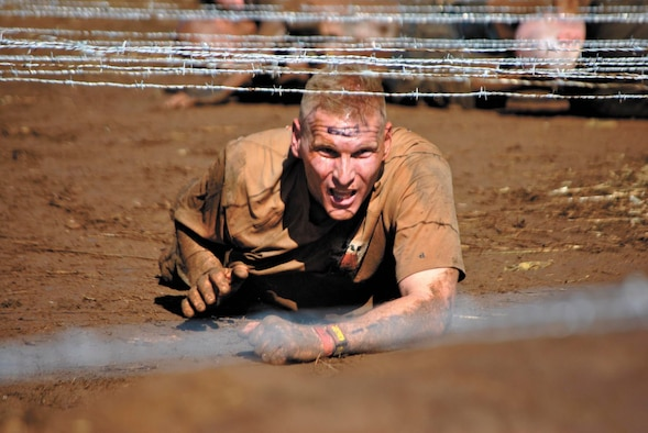 Jeffrey Greenwood, lieutenant colonel and commander of the 323rd Training Squadron, endures the low-crawl event during the 15-obstacle Spartan Sprint Race Saturday in Burnet, Texas. (U.S. Air Force photo/Nicole Greenwood)
