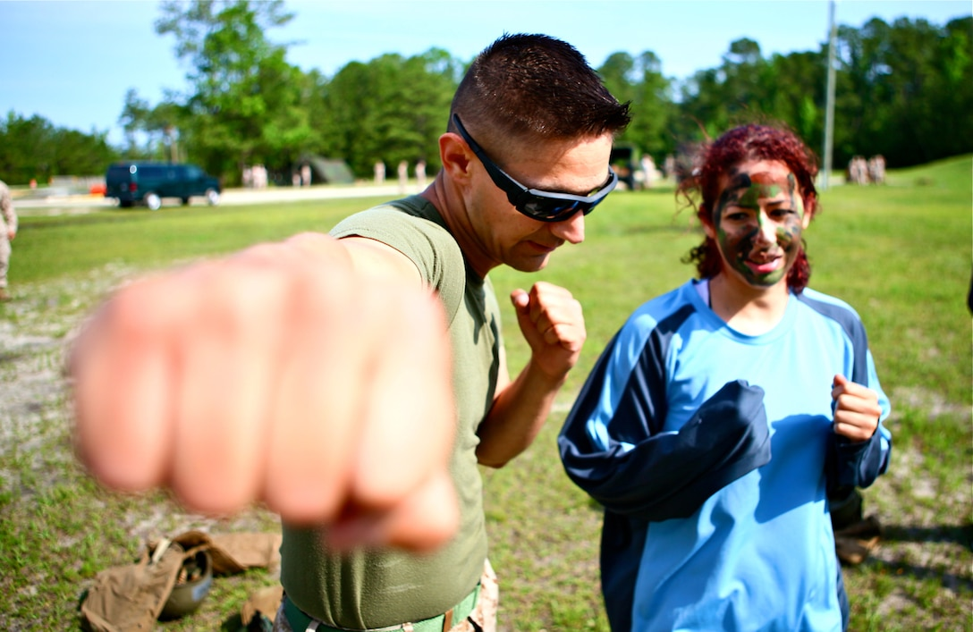 Corporal Andrew J. Leonard, a green belt instructor in the Marine Corps Martial Arts program, 2nd Radio Battalion, teaches tan belt techniques to Maria Marin, a Marine wife, during 2nd Radio Battalion's Jane Wayne Day, aboard Marine Corps Base Camp Lejeune, N.C., May 19, 2012.Throughout the day wives, children and one husband took part in MCMAP, physical training, rides in military vehicles and firing weapons. (U.S. Marine Corps photo by Cpl. Daniel A. Wulz)