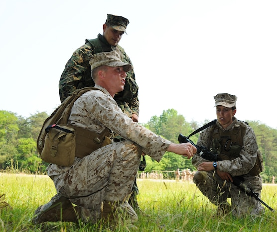 Second Lt. Jonathan Bowman, squad leader for 2nd Squad, 4th Platoon, Charlie Company, The Basic School, briefs his squad on the scheme of maneuver during a foot patrol exercise at Landing Zone 7, May 25. There to assess his mission brief is Sgt. Jose Zepata, a combat instructor, Dugout Platoon, Combat Instructor Company, TBS.