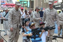 Children check out weapons during Marine Day in Times Square, May 26. Marine Day is part of Fleet Week New York 2012, where Marines and sailors show New Yorkers Marine Corps weapons, equipment and culture.