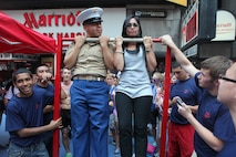 Pfc. Gael Burgoa and civilian New Yorker Camille Goldner do flexed-arm-hangs side-by-side during Marine Day in Times Square, May 26. Marine Day is part of Fleet Week New York 2012, where Marines and sailors show New Yorkers Marine Corps weapons, equipment and culture.::r::::n::