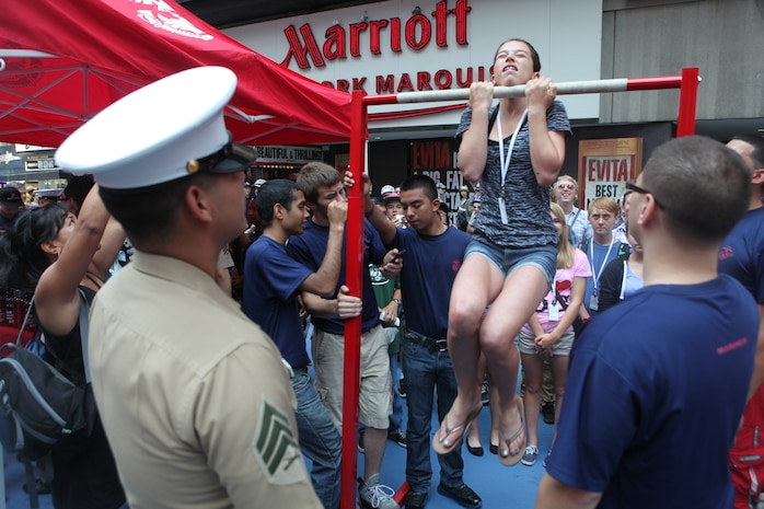 Jenna Holcomb, a student at Mcauliffe Middleschool, performs a flexed-arm-hang during Marine Day in Times Square, May 26. Marine Day is part of Fleet Week New York 2012, where Marines and sailors show New Yorkers Marine Corps weapons, equipment and culture.