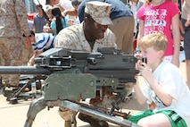 Lance Cpl. Mamadou Tamboura, and infantryman with 1st Battalion 9th Marines, shows New York children the Mark 19 grenade launcher during Marine Day in Times Square, May 26. Marine Day is part of Fleet Week New York 2012, where Marines and sailors show New Yorkers Marine Corps weapons, equipment and culture.