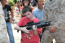 Jacob Lafidas, a civil air patrol cadet, handles an M203 grenade launcher for the first time during Marine Day in Times Square, May 26. Marine Day is part of Fleet Week New York 2012, where Marines and sailors show New Yorkers Marine Corps weapons, equipment and culture.