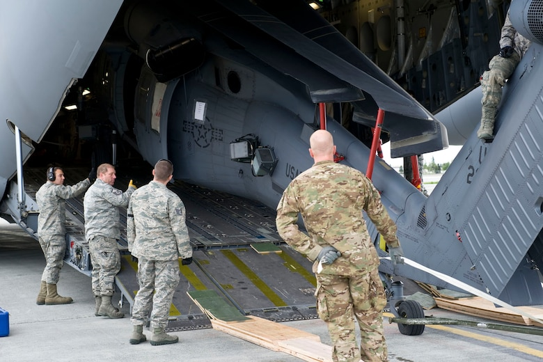 """JOINT BASE ELMENDORF-RICHARDSON, Alaska - Members of the Alaska Air National Guard's 176th Wing load an HH-60 """"Pave Hawk"""" search and rescue helicopter onto a C-17 """"Globemaster III"""" for a 120-day deployment to Afghanistan May 28, 2012. The helicopter is a part of a package of equipment and crew that is deploying in support of Operation Enduring Freedom. National Guard photo by Capt. John Callahan."""