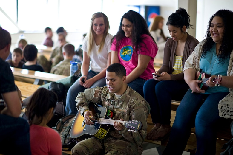 JOINT BASE ELMENDORF-RICHARDSON, Alaska - Senior Airman Donald Haretuku, an aircrew flight equipment specialist for the Alaska Air National Guard's 176th Operations Support Squadron, plays the guitar and sings with family and friends while waiting to depart Alaska for Afghanistan May 28, 2012. More than 180 members of the Alaska Air National Guard's 176th Wing are deploying for about 120 days in support of Operation Enduring Freedom. (National Guard photo by Master Sgt. Shannon Oleson)