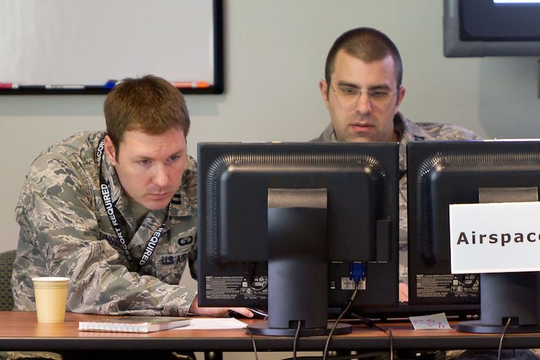 BEDFORD, Mass. - Capt. Tom Bilingsley (left) and Capt. Brendan Simison, operators from the 102nd Air Operations Group, Otis ANGB, Mass., evaluate a prototype initiative during a demonstration last month. During the demonstration, the Electronic System Center was assessing the capabilities of the Deliberate and Dynamic ISR Management, or D2ISRM, initiative to improve command and control of intelligence, surveillance and reconnaissance data. (Courtesy photo).