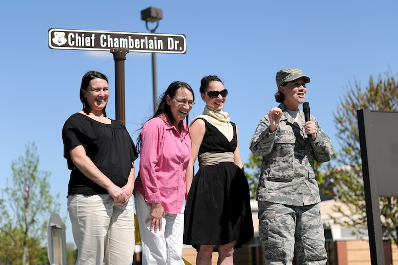 The daughters of retired Chief Master Sgt. Robert C. Chamberlain share a laugh during a ceremony held recently at Hancock Field Air National Guard Base during which a street was named in honor of their father. Chief Chamberlain served 32 years in the miliary, ending his career in the Civil Engineering Squardron at the 174th Fighter Wing.  The cermony was officiated by Maj. James Oaksford, the current CES Commander, who helped spearhead the effort to dedicate the street in Chief Chamberlain's honor.  (Photo by Tech. Sgt. Ricky Best/Released)