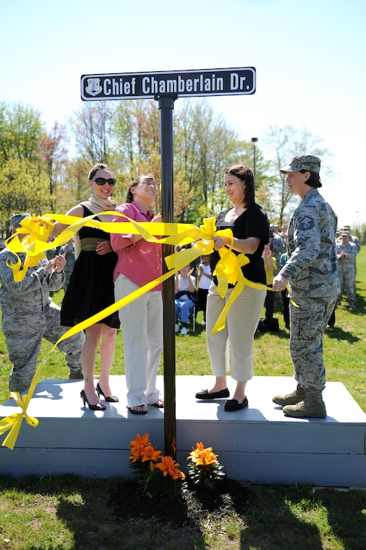The daughters of retired Chief Master Sgt. Robert C. Chamberlain help cut the ribbon on a new street at Hancock Field Air National Guard Base named in honor of their father. Chief Chamberlain served 32 years in the miliary, ending his career in the Civil Engineering Squardron at the 174th Fighter Wing.  The cermony was officiated by Maj. James Oaksford, the current CES Commander, who helped spearhead the effort to dedicate the street in Chief Chamberlain's honor.  (Photo by Tech. Sgt. Ricky Best/Released)