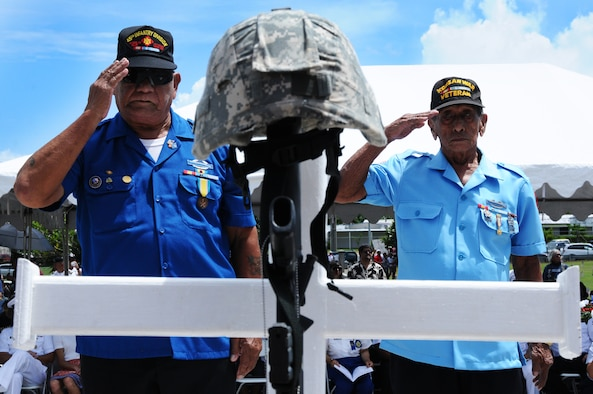 ANDERSEN AIR FORCE BASE, Guam- Tony Calvo and William Quenga of the Korean War Veterans Association present a salute to the cross honoring Korean War veterans during the Guam Veteran Cemetery Memorial May 28. The crosses honored seven wars of the American history ranging from World War I to the war in Iraq. (U.S. Air Force photo by Senior Airman Carlin Leslie/Released)