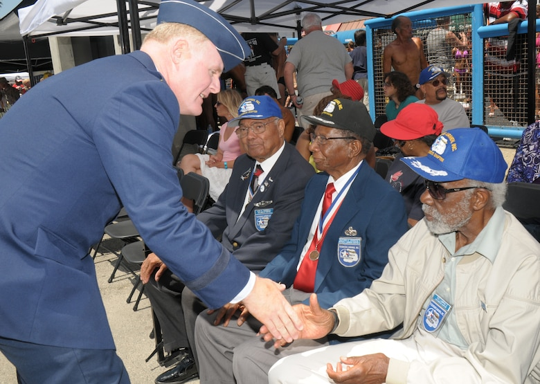 Brigadier Gen. Roger Teague, Space and Missile Systems Center vice commander, shakes hands with Tuskegee Airman Ted Lumpkin. Four surviving members of the Tuskegee Airmen's Red Tail Squadron were honored during the Muscle Beach Classic, May 28. (Photo by Joe Juarez)